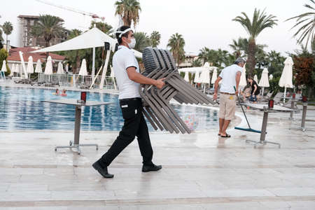 Belek, Turkey - October 2020: Hotel staff wearing face masks in an all-inclusive hotel. Safety measures in five star all-inclusive Antalya resort during global pandemic. Man carrying bunch of chairs. 新闻类图片