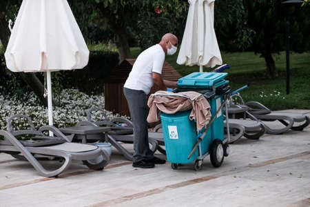 Belek, Turkey - October 2020: Hotel staff wearing face masks in an all-inclusive hotel. Safety measures in five star all-inclusive Antalya resort during global pandemic. Janitor cleaning territory. 新闻类图片