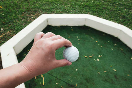 White hand holding golf ball in its hole at field. Playing mini golf on artificial green grass outdoors. Setting goals and winning concept. Fun vacation entertainment for families. Minigolf setting. 免版税图像