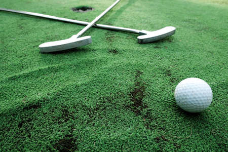 Fun vacation entertainment for summertime. Playing mini golf on green grass outdoors. Setting goals and winning lifestyle concept. Competition at golf course: two crossed sticks. Blank space for copy.