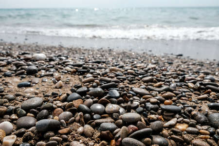 Variety of smooth pebbles, rocks and stones at seashore. Quiet peaceful beach with water waves coming in. Escaping to dream vacation for weekend getaway. Good summer vibes for recreational pursuit.