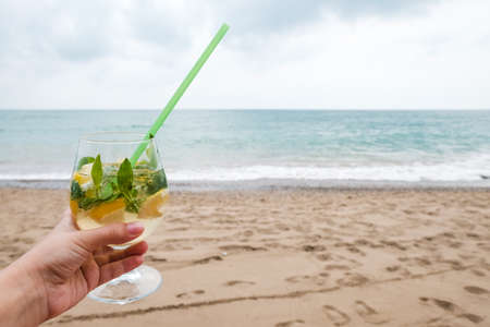 Luxury drink on sunny beach near the sea. Waves and sand in background. White female hand holding a wine glass with tropical mojito cocktail. Recreational getaway or romantic holiday on remote island.