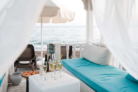 Belek, Turkey - October 2020: Luxury VIP lounge with curtains and beds on the beach near Mediterranean sea. Champagne and pizza near sunbeds, sea in background. Romantic summer getaway for honeymoon. 新闻类图片