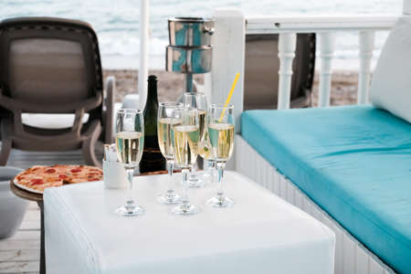 Luxury VIP lounge for rich tourists on a beach near Mediterranean sea. Champagne and pizza near sunbeds, sea in background. Romantic summer getaway for honeymoon or anniversary. Vacation with friends