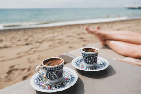 Luxury beach vacation for couple in Turkey. Two cups of Turkish coffee, female legs, sand and Mediterranean sea in background. Romantic holiday getaway for two. Summer day or morning at Antalya coast.