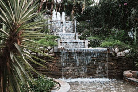 Belek, Turkey - October 2020: Beautiful waterfall with statue on all-inclusive hotel territory. Luxury vacation in idyllic surroundings. Water flowing down outdoors at a romantic resort in Antalya.
