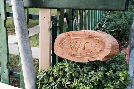 Brown wooden board with carved WC sign and arrow to show direction to a public bathroom. Beautiful signboard near green fence outdoors. Path for people to wash hands in a washroom or restroom.