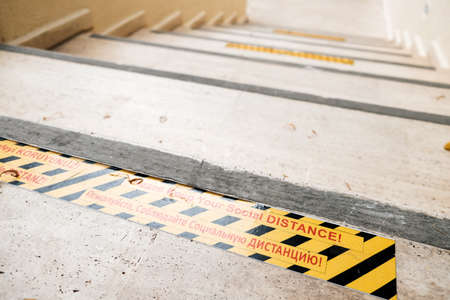 Please keep your social distance! Warning on the floor on stairs during coronavirus. Global pandemic safety precautions around the world. Multilingual message for distancing in bright yellow and black