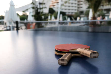 Close up view of two table tennis rackets on blue surface. Selective focus, hotel or park in blurred background. Fun competition for two or entertainment on vacation. Active lifestyle concept. 免版税图像