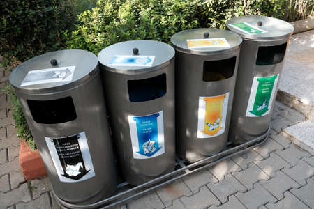Belek, Turkey - October 2020: Four various trash bins for recycling waste outside. Separate buckets for plastic, paper, glass, non-recyclable things. Eco friendly lifestyle for environment protection.