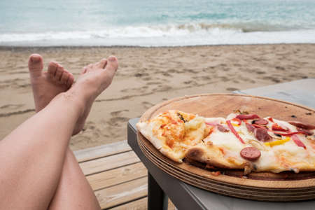 Young Caucasian woman lying at the beach eating pizza. Legs and Italian food slices, sea in background. Careless holidays at all inclusive resort. Luxury recreational vacation concept at Mediterranean