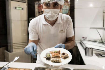 Belek, Turkey - October 2020: Man in face mask and gloves serving Turkish baklava for tourists at all-inclusive hotel in Turkey. Delicious traditional sweets put on a plate by staff.