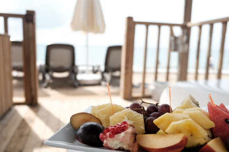 Delicious fruit plate served in a vip lounge of luxury resort. Traveling to remote island for weekend retreat. Selection of tropical fruits near the ocean. Perfect romantic paradise honeymoon at sea. 免版税图像