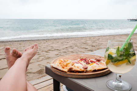 Young Caucasian woman lying at the beach eating pizza and drinking cocktail. Legs, sea in background. Careless holidays at all inclusive resort. Luxury recreational vacation concept at Mediterranean