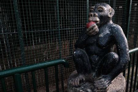Fun statue of black chimpanzee near monkey cages in a zoo. Stone ape sitting on a stump eating red apple and welcoming tourists and visitors to zoological garden.