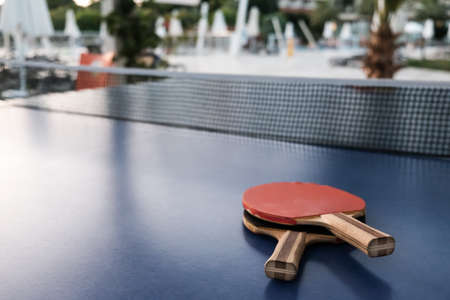 Closeup view of two table tennis rackets with net on blue surface. Selective focus, hotel or park in blurred background. Fun competition for two or entertainment on vacation. Active lifestyle concept