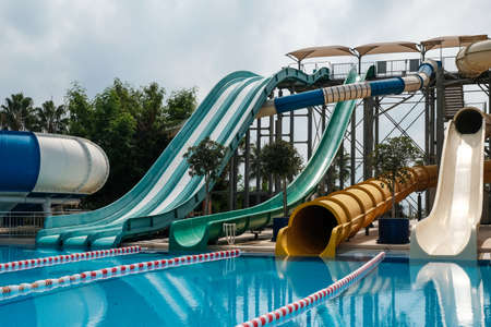 Fun fast slides in an aquapark. Summer vacation entertainment ideas. Colorful slide variety and turquoise swimming pool at a hotel. Water reflection in empty aqua park during pandemic isolation.