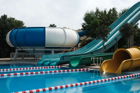 Side view of fun slides in aquapark. Summer vacation entertainment ideas. Colorful slide variety and turquoise swimming pool at a hotel. Water reflection in empty aqua park during pandemic isolation.