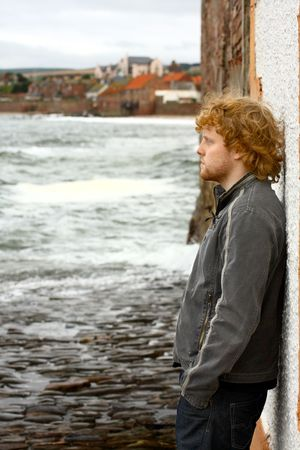 lonely boy: Young, depressed man and the sea Stock Photo