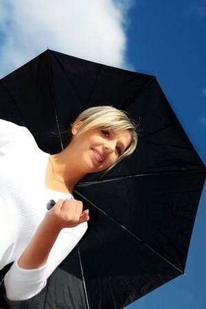 A beautiful woman with black umbrella on sunny day photo