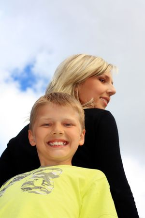 Happy mother and son smiling, against blue sky on sunny day photo