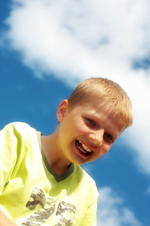 Ten year old boy laughing against blue sky photo