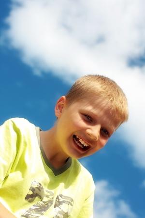 joyfull: Ten year old boy laughing against blue sky Stock Photo