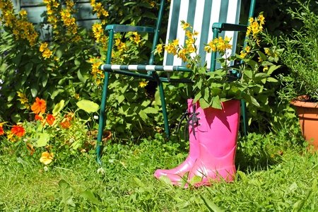 wellingtons: Pink wellingtons and chairdeck in the garden on sunny day Stock Photo
