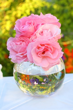 Lovely pink roses in a glass  vase in the garden  photo