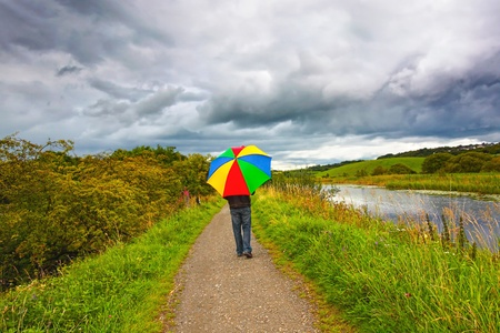 A man walking in the rain along Forth and Clyde Canal, Scotland Stock Photo