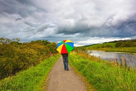 lloviendo: Un hombre que camina en la lluvia a lo largo del Canal Forth y Clyde, Escocia