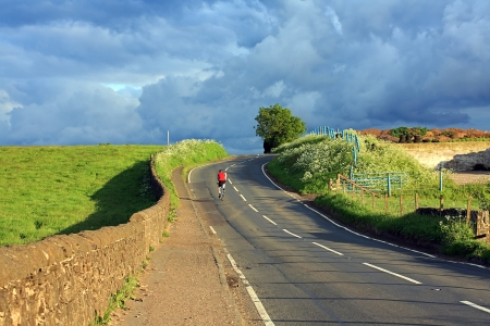 sunglight: Beautiful Scottish road with a lonely cyclist in the countryside Stock Photo