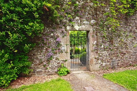 victorian style: Old, stone garden wall with  metal gate