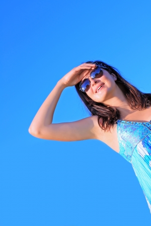 A pretty woman in sunglasses looking up against blue sky photo