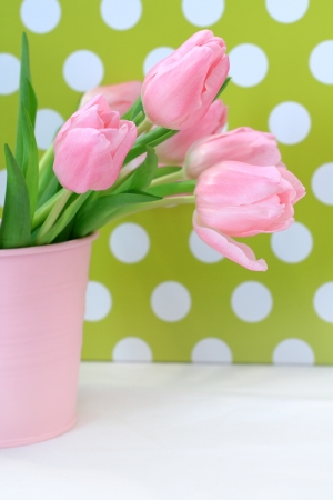 Beautiful tulips in a pink vase against polka dots background