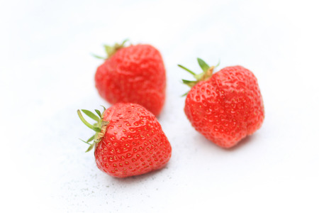 strawberies: Fresh strawberies close up on white painted background Stock Photo