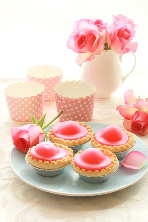 Beautiful roses and fresh pink cakes still life photo