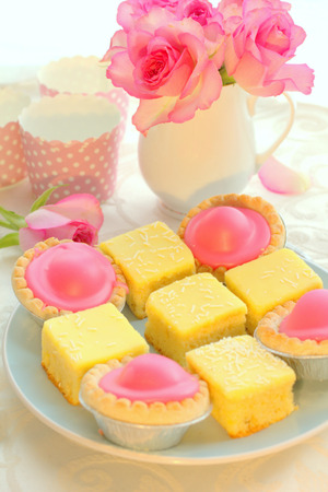 Beautiful colorful cakes and pink roses, still life photo