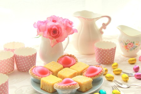 Easter table with sweet eggs, pink roses and fresh cakes photo