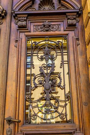 Old Weathered wooden door with vintage floral pattern metalwork