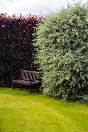 garden bench: Brown garden bench with green grass Stock Photo