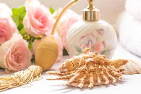 Bath arrangement with parfume bottle, folded towels and pink roses Stock Photo