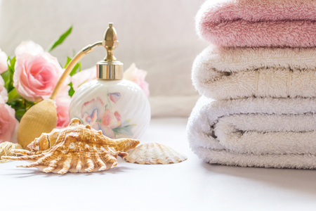 cleaness: Bath arrangement with parfume bottle, folded towels and pink roses Stock Photo