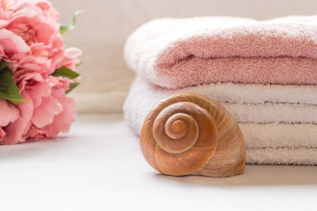 Folded towels on bathroom counter with flowers Stock Photo