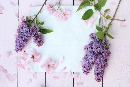Mooie, lente romantische achtergrond met wit papier, lila en kersenbloemen