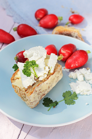 vibrant cottage: Fresh healthy breakfast, a slice of soda bread with butter and cottage cheese and red radish Stock Photo