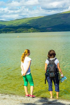 loch lomond: Teenage girls standing at the beach, summer at Loch Lomond, Luss, Scotland