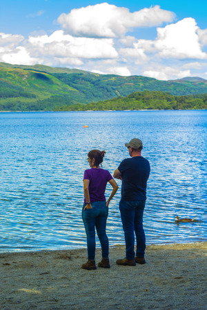 loch lomond: A couple standing on the beach at Loch Lomond, Argylle and bute in Scotland