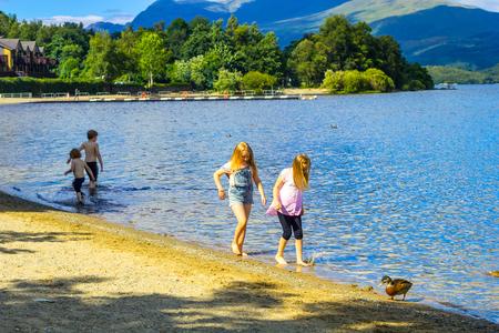two girls: Two girls walking along the beach on summer at Loch Lomond, Luss, Scotland, UK Editorial