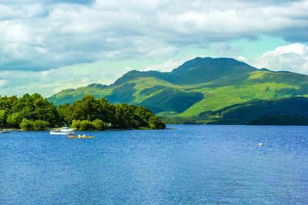loch lomond: Canoe on calm blue Loch Lomond lake  in Luss in Scotland, UK